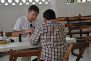 Pater Bennet befragt die Patienten und nimmt ihre Daten auf.